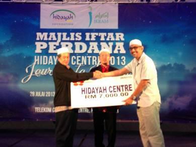 Timbalan Pengerusi Yayasan Bunga Raya menyampaikan mock cheque pada Presiden IKRAM disaksikan Pengerusi HC Foundation